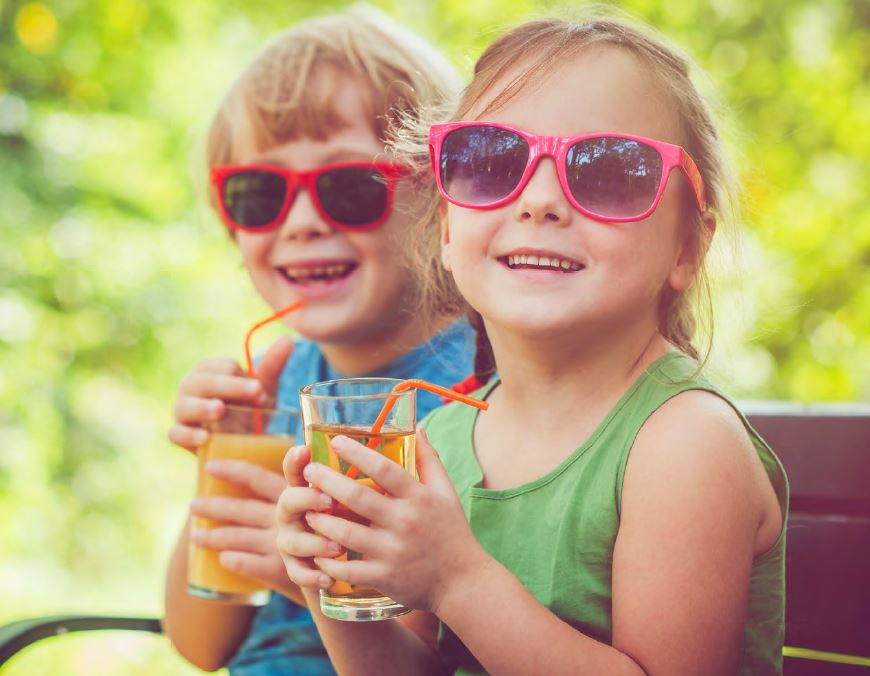 Image of two kids in sunglasses holding drinks