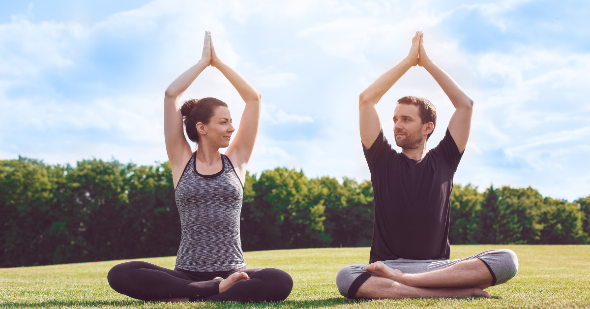 two people practicing yoga outside