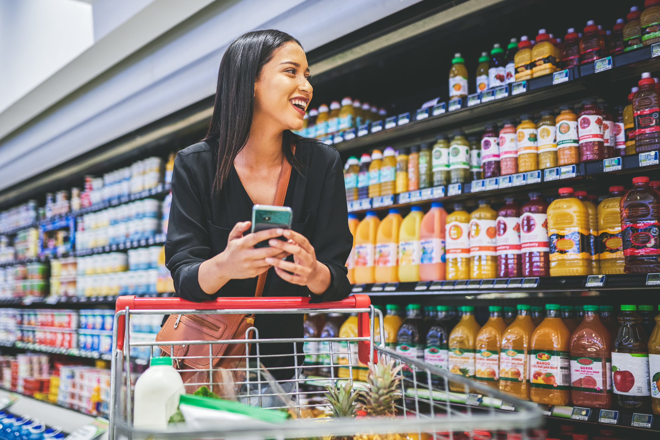 Shot of a young woman using a smartphone while shopping in a grocery store
